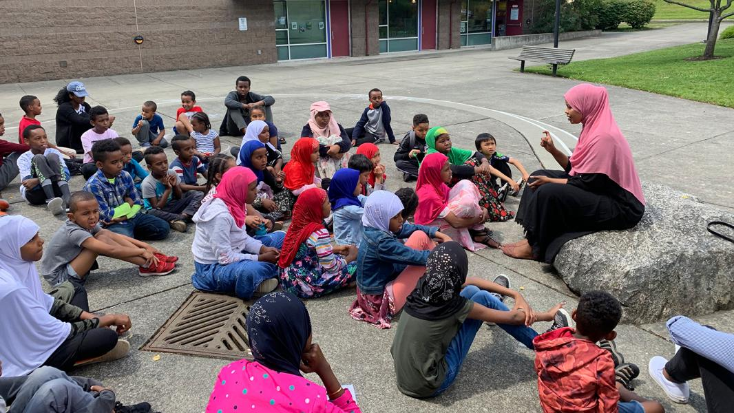 East African Community Services' students sit listening to a teacher in an outside setting, July, 2019, SeaTac, WA