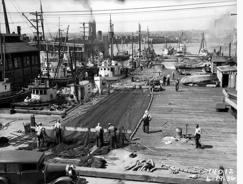 Fishermen repair nets spread out on the docks , Seattle, ca. June 19, 1936