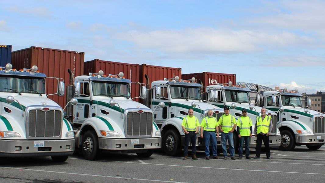 Castan empployees pose in front of big rig semi-trucks on a sunny day in south Seattle
