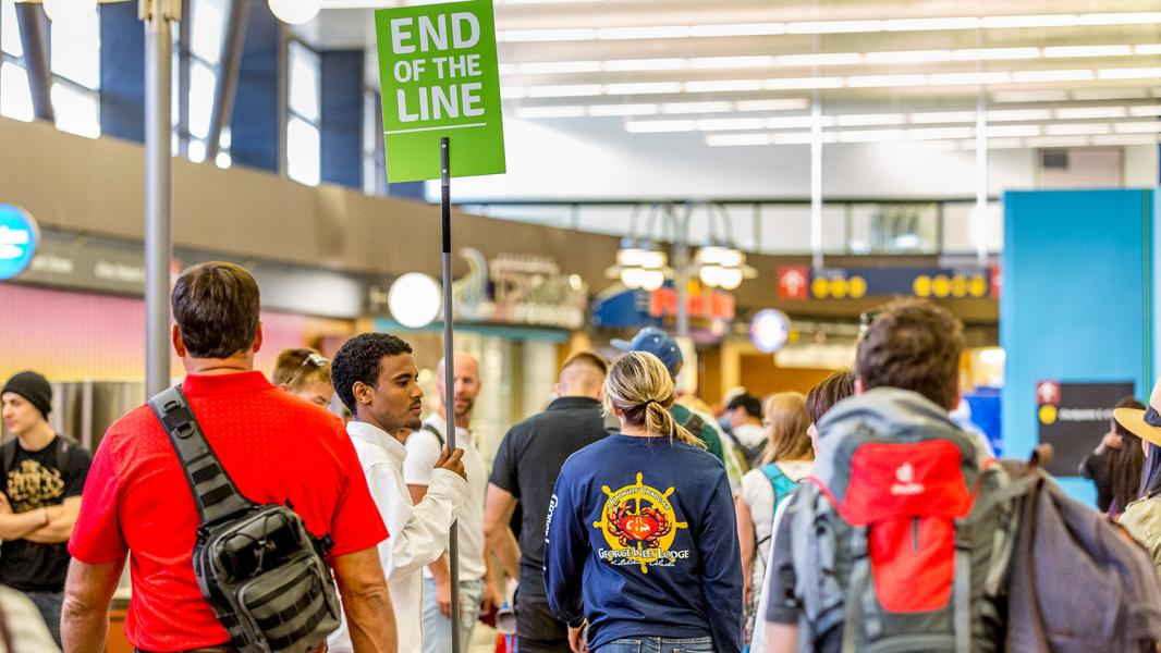 "A Sea-Tac Airport ""Pathfinder"" holds an ""End of Line"" sign to indicate where security checkpoing lines can be joined by newly arrived passengers, Aug., 2016"