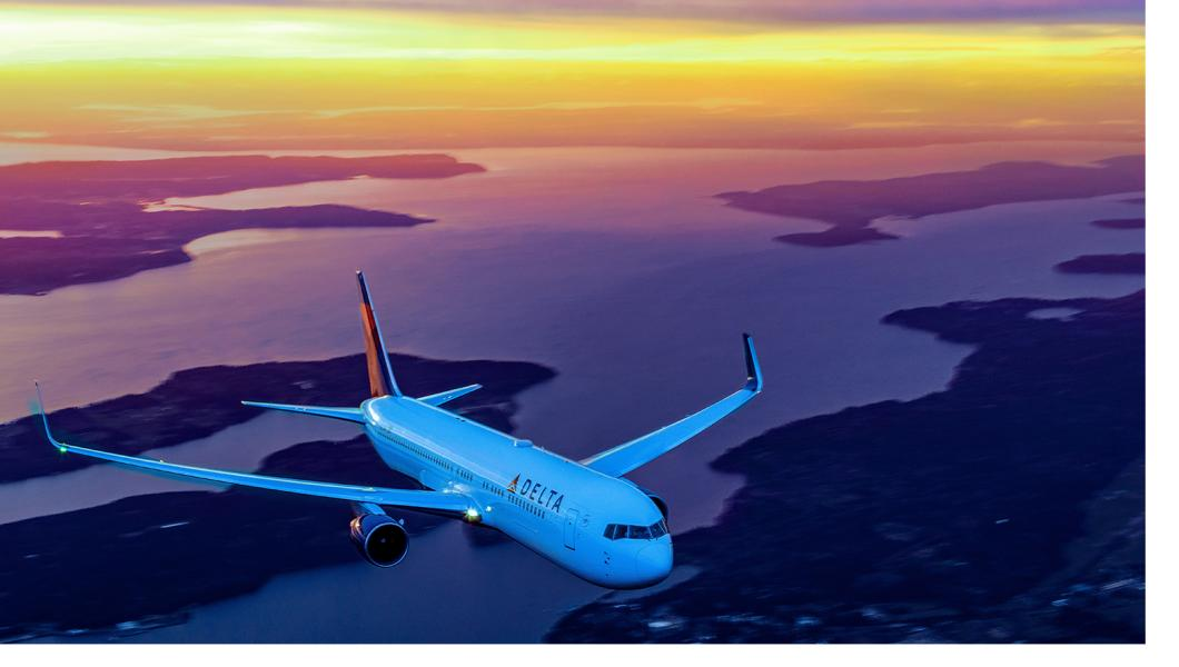 Delta aircraft in flight with beautiful sunset