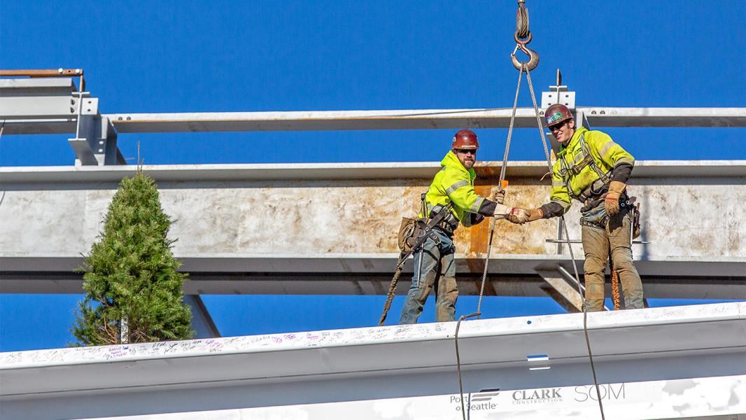 Tradesmen shake hands after guiding the final beam into place on the International Arrivals Facility at Sea-Tac Airport December 4, 2018
