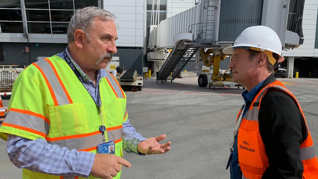 Paul Pelton talks with Commissioner Steinbrueck on the airfield at Sea-Tac Airport