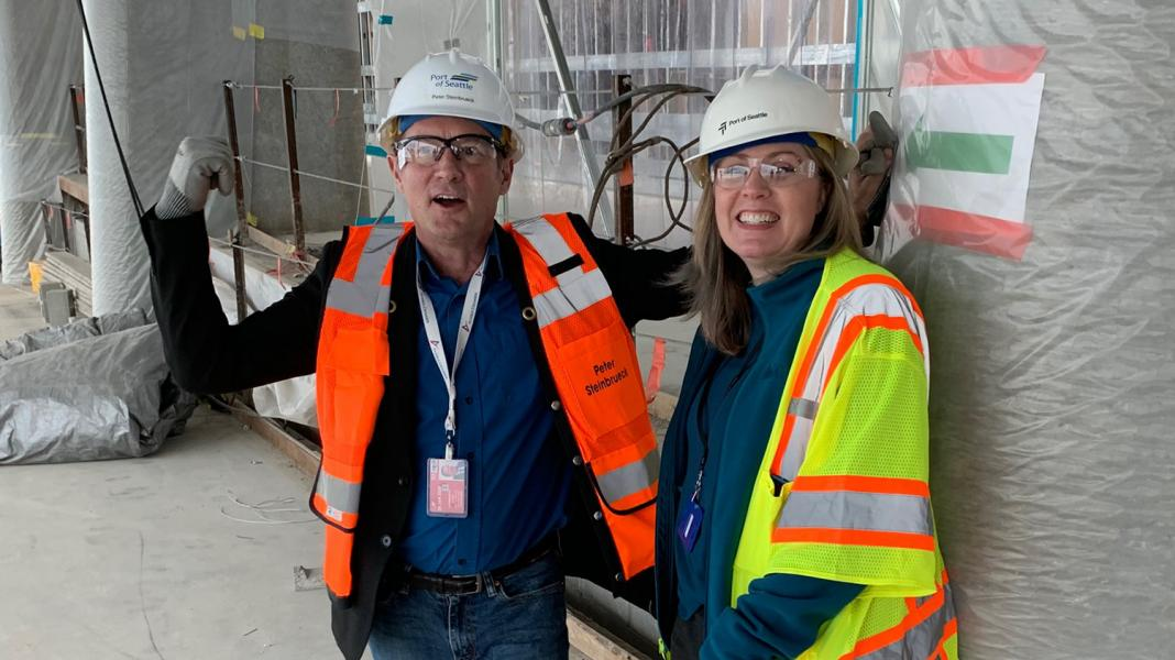 Janet Sheerer and Commissioner Steinbrueck in the new International Arrivals Facility under construction at Sea-Tac Airport, April, 2019