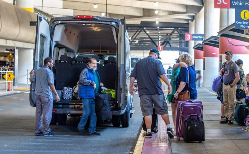 Shuttle passengers disembark from a shuttle at Sea-Tac Airport, June, 2018